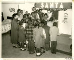 """Photograph of Dorothy F. Steele with sixth grade elementary students and Santa"""